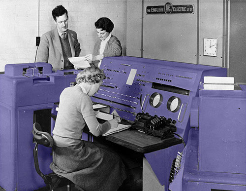 Researchers gathered around an early computer console